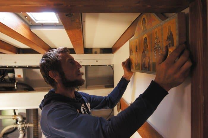 Плотник Ярослав, будущий капитан, выбирает место для икон в трюме