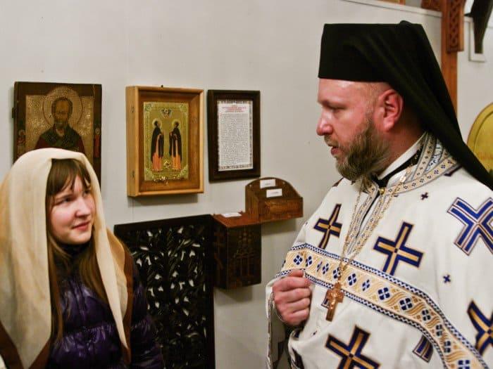 Отец Никита рассказывает Майе Яковлевой о подаренной храму чудотворной иконе Петра и Февронии Муромских, с частицей мощей. Фото Виталия Каплана.