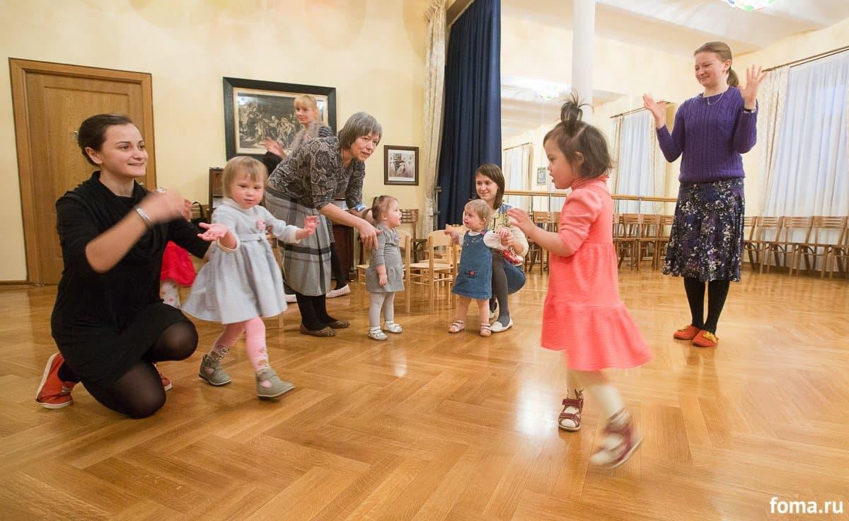 Музыкальное занятие в большом зале дома. Света освоила движения и теперь радостно их повторяет