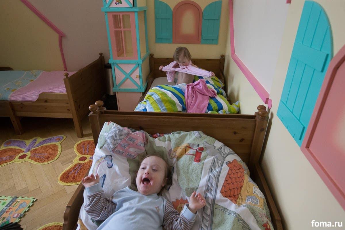 Подготовка к дневному сну. Ксюша уже переоделась и радуется, а Света все никак не может справиться с рукавами пижамы. В комнате у нее есть свой отдельный шкафчик и свои полочки в большом гардеробе. У нее своя личная одежда и свое постельное белье. Для детишек с синдромом Дауна особенно важно, чтобы была стабильность. В мелочах и личных вещах — тем более