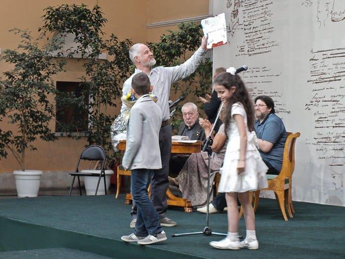 Художник Константин Сутягин получил из рук детей свой наградной диплом, который сами же дети и рисовали