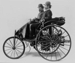 """Karl Benz with his Assistant Josef Brecht in """"patent-Motorwagen"""" of 1886."""