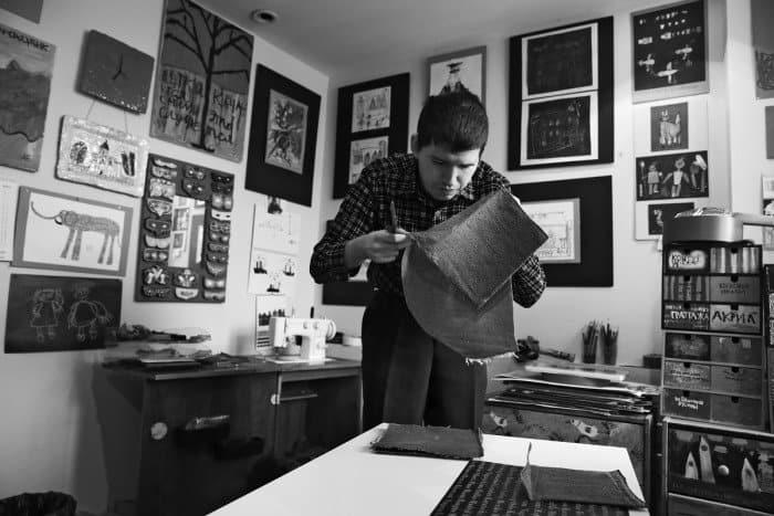 Илья вырезает квадраты для панно «Особые художники». В свое время попросили всех, кто может, принести старые джинсы и теперь делают из них подушки, кораблики, принты для сумок