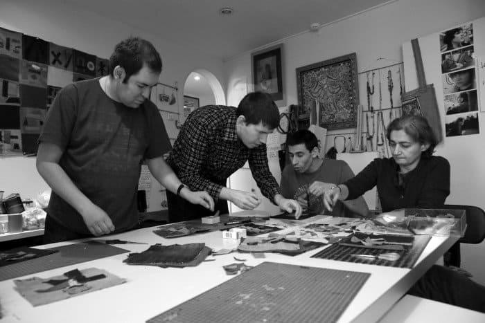 «Юрий, Илья, Ратмир и Ануш выкладывают аппликации, подбирают элементы по цвету, как им нравится. Важно, чтобы это был их выбор. Потом этими элементами будет наставляться панно «Особые художники» (на заднем плане)».