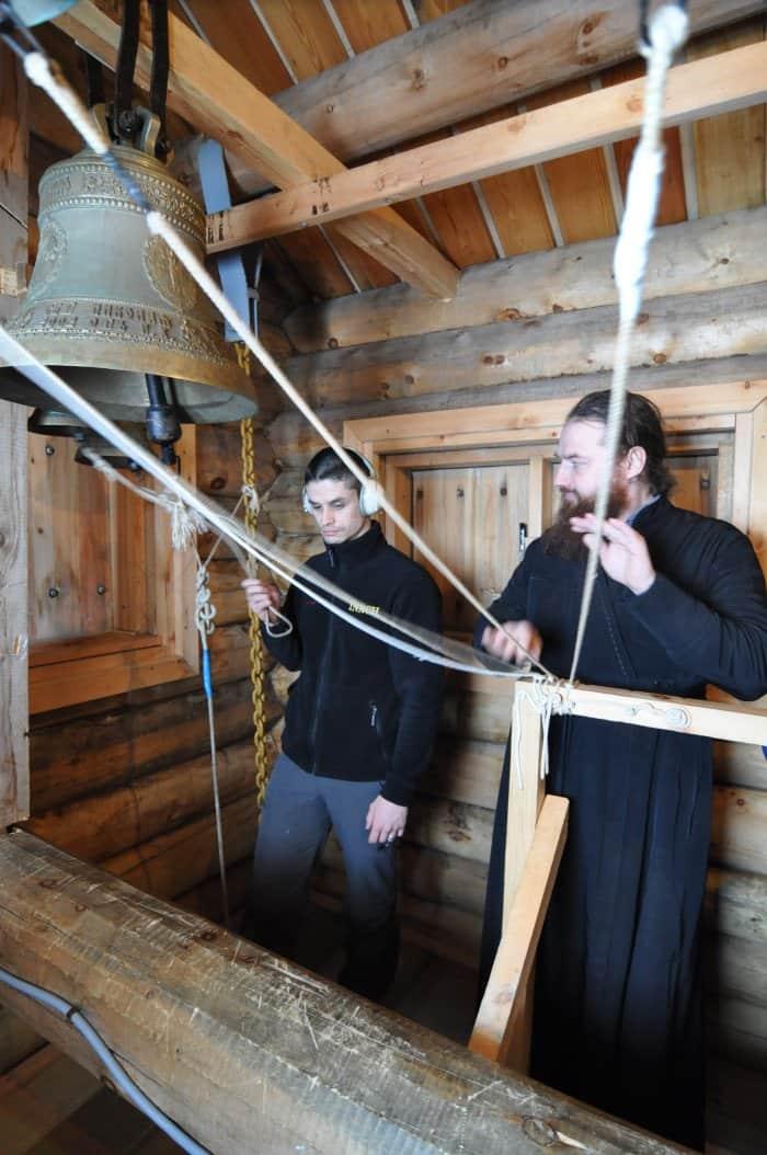 Отец Вениамин обучает чилийского полярника колокольному звону