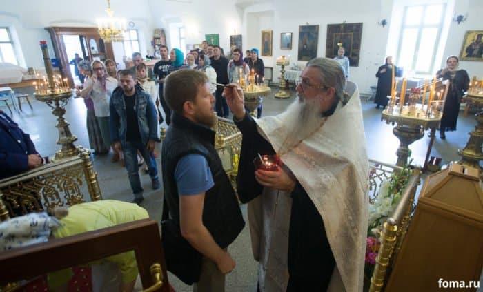 После молебна священник помазывает паломников елеем из лампадки у Креста. Фото Юлии Маковейчук