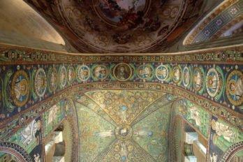 Мозаика свода базилики Сан-Витале, Равенна, Италия, VI в.  Базилика была заложена в 527 году, освящение храма состоялось в 548 году. Все внутреннее мозаичное убранство церкви было создано одновременно в 546—547 годы предположительно различными мастерами. Свод украшен медальоном с изображением апокалипсического Агнца (Откр. 5:12), поддерживаемого четырьмя ангелами, символизирующими стороны света. Белоснежный агнец, увенчанный нимбом, изображен на фоне звёздного неба, медальон с ним обрамлён венком. Композиция окружена райскими деревьями, растениями, птицами и животными.  Фото Sgt. Pepper57/Flickr/CC BY 2.0