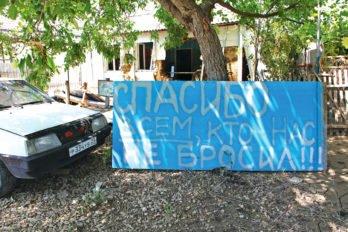Надпись на обломках забора разрушенного наводнением дома. Фото Владимира Ештокина