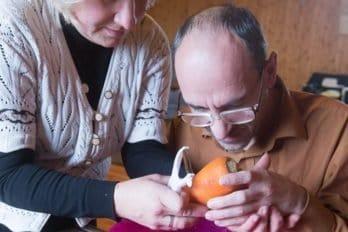 Светлана помогает Сергею - учит как правильно чистить морковь.