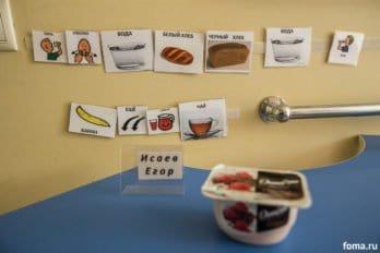 На стене возле обеденного стола укаждого ребенка прикреплены карточки на липучках сизображением простых видов еды, действий ипросьб. Во-первых, во время еды воспитатели четко называют то, что вэтот момент ест ребенок, ипоказывают карточку. Во-вторых, дети сами должны отвечать на вопросы, показывая или отрывая нужную картинку