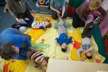 Групповое занятие под музыку. Деткам делают легкий массаж, комментируя действия иназывая части тела