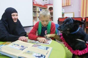 Собака Лиза иматушка Лия вгородской библиотеке на занятиях для детей спроблемами чтения — помогают Максу научиться читать. Инокиня Лия руководит социально-миссионерским направлением деятельности скита, одним из проектов которого является собачий приют «Радово-Островок. Территория открытого сердца». Вприют попадают собаки снеблагополучной историей: кого-то выгнали на улицу хозяева, над кем-то жестоко издевались. Вприюте они получили кров икорм, асестры провели ссобаками немало часов на курсах по обучению четвероногих для канис-терапии сдетьми