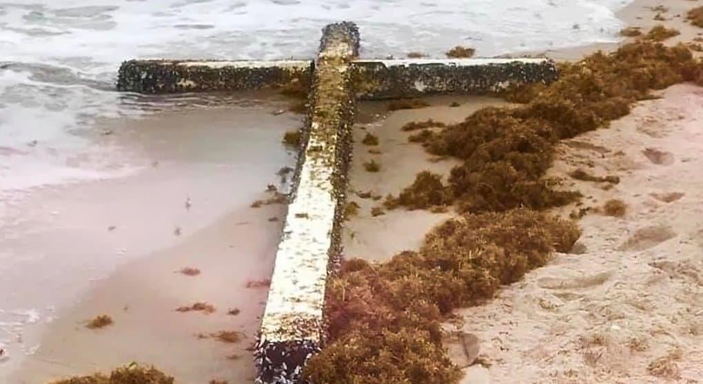 Туристы молятся у креста, выброшенного волнами на пляж Флориды